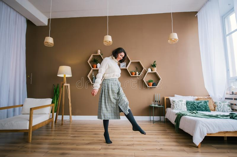 A young smiling woman in white sweater dances in a home room royalty free stock images