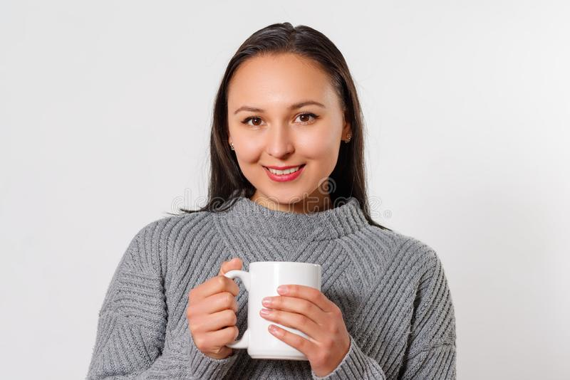 Young smiling brunette woman girl in a warm sweater with a cup of hot coffee. on white stock photo