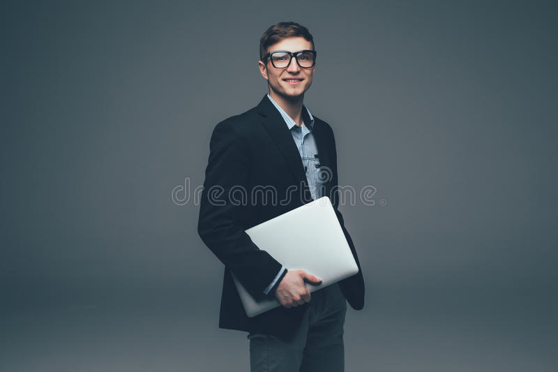 Young smiling business man holding laptop on grey. Background royalty free stock image