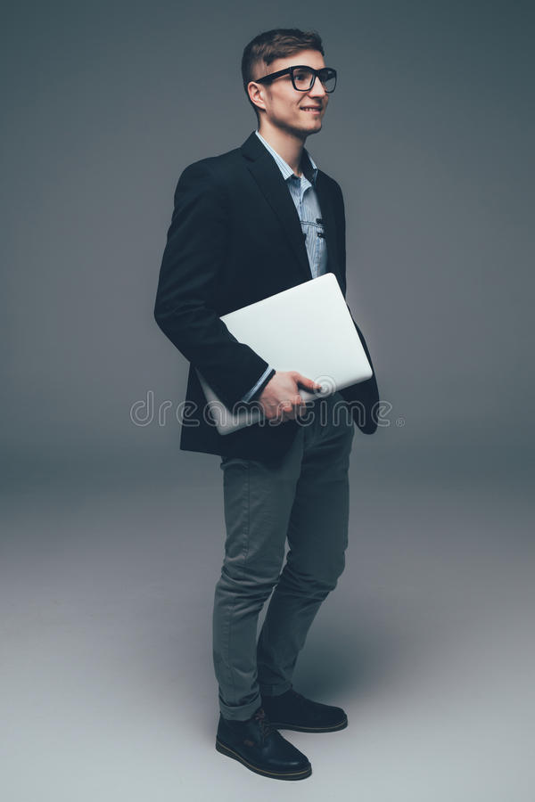 Young smiling business man holding laptop on grey. Young smiling business man holding laptop and move stock photos