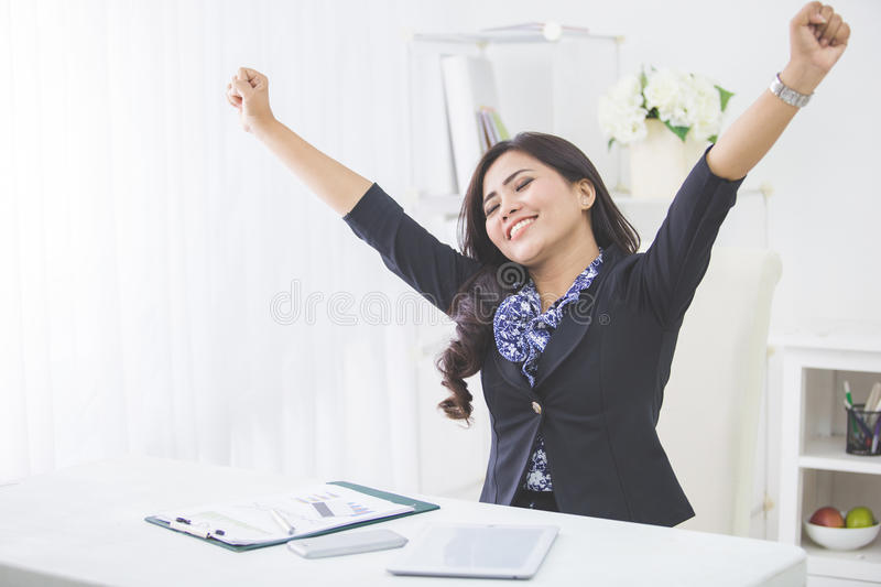 Young smiling business woman raise arm after finishing her work royalty free stock images