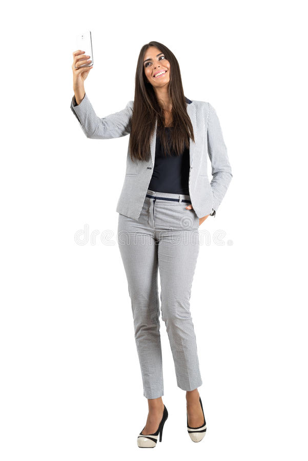 Young smiling business woman taking selfie with mobile phone stock image
