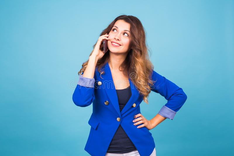 Young smiling business woman talking oh the phone, on blue background stock photography