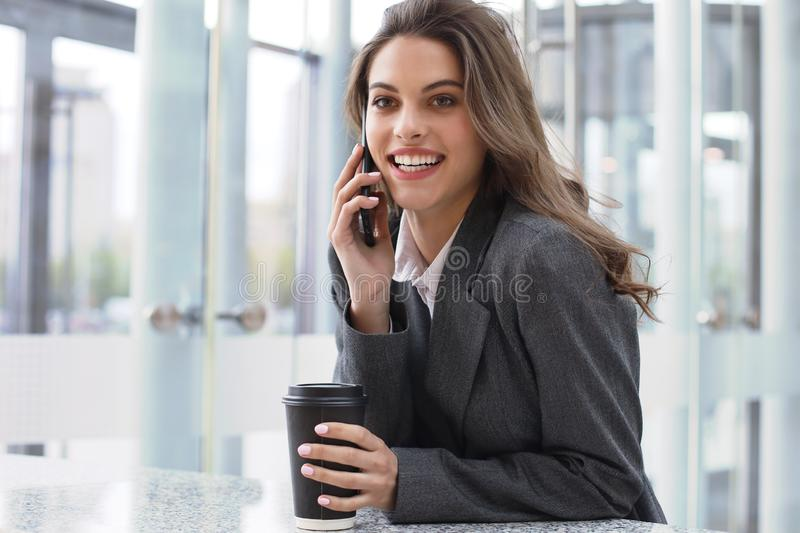 Young smiling business woman using smartphone near computer in office stock images