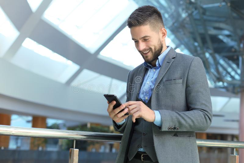 Young smiling businessman calling on phone at office stock images