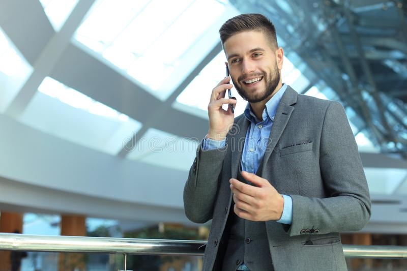 Young smiling businessman calling on phone at office stock photos
