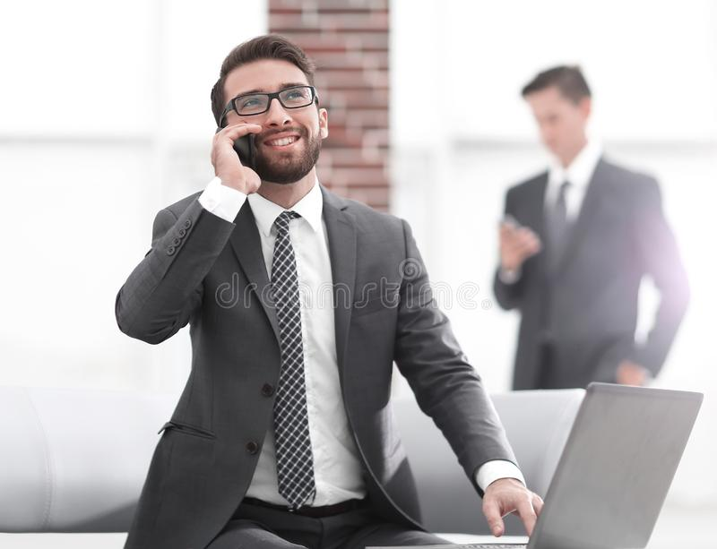 Confident young man talking on phone in office stock photography
