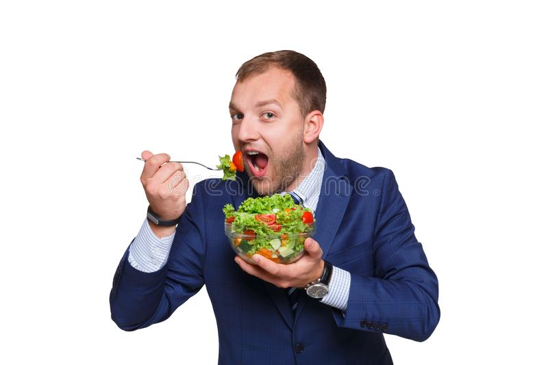 Young smiling businessman eating green salad isolated on white background. Healthy food delivery, diet concept royalty free stock image