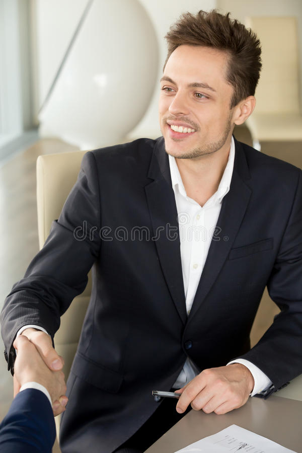 Young smiling businessman shaking male hand at meeting, first im. Young smiling businessman wearing black suit shaking male hand at meeting, nice to meet you at stock photos