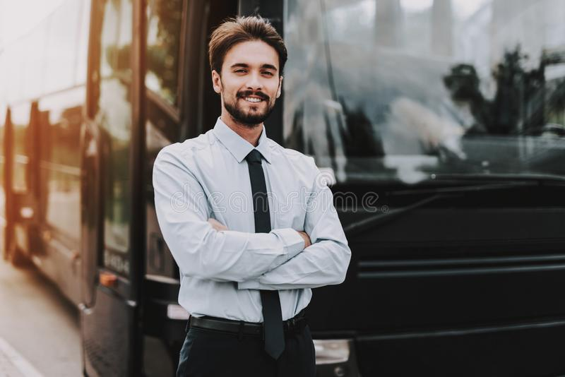 Young Smiling Businessman Standing in front of Bus. Confident Attractive Man wearing White Shirt and Black Tie with Crossed Arms Standing in front of Tour Bus royalty free stock image