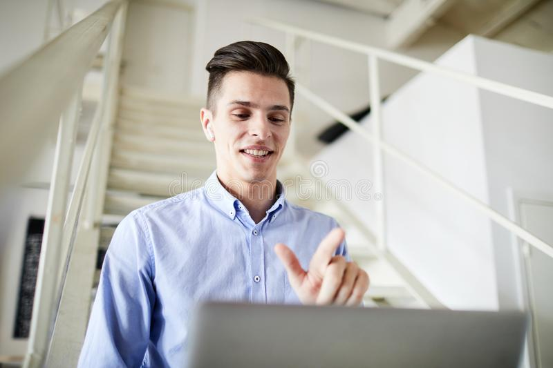 Video communication. Young smiling businessman talking through video-chat while sitting in front of laptop royalty free stock images