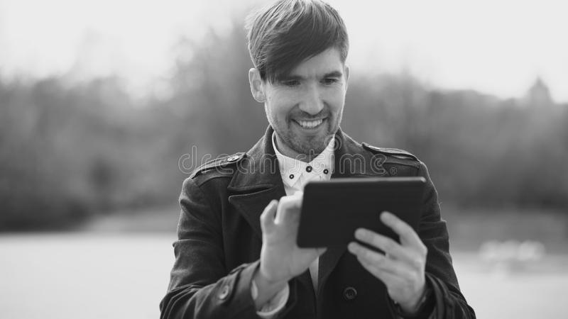 Young smiling businessman using tablet computer during break at the street. Young smiling businessman using tablet computer during break royalty free stock photos