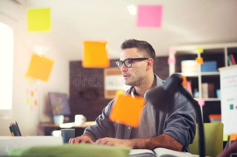 Young smiling businessman working in office. Handsome young smiling businessman working in office royalty free stock image
