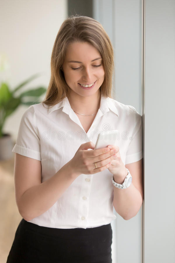 Young smiling businesswoman checking phone, texting message, usi. Ng business apps for mobile payment and online shopping, m-banking application, communicating royalty free stock image