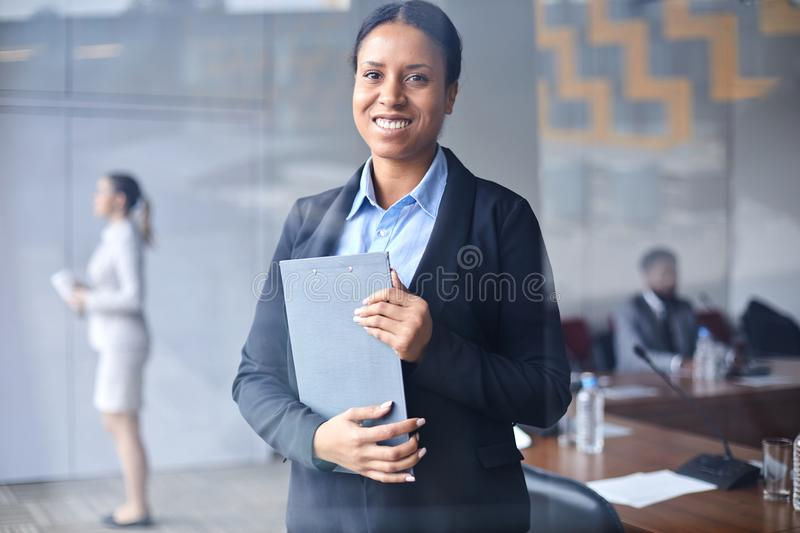 Female delegate. Young smiling businesswoman with clipboard looking at you in conference hall on background of colleagues royalty free stock image