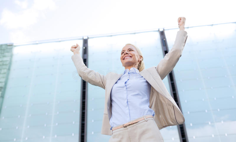 Young smiling businesswoman over office building. Business, people and education concept - young smiling businesswoman over office building royalty free stock photography
