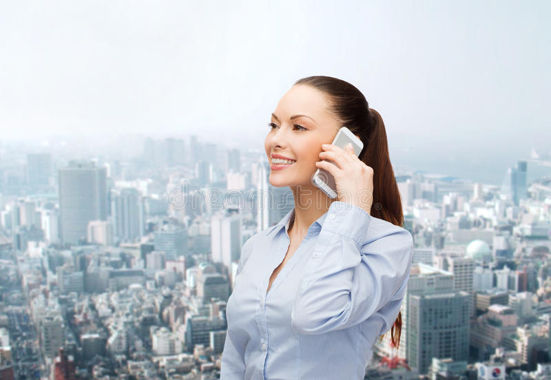 Young smiling businesswoman with smartphone. Business, technology and education concept - friendly young smiling businesswoman with smartphone stock photo