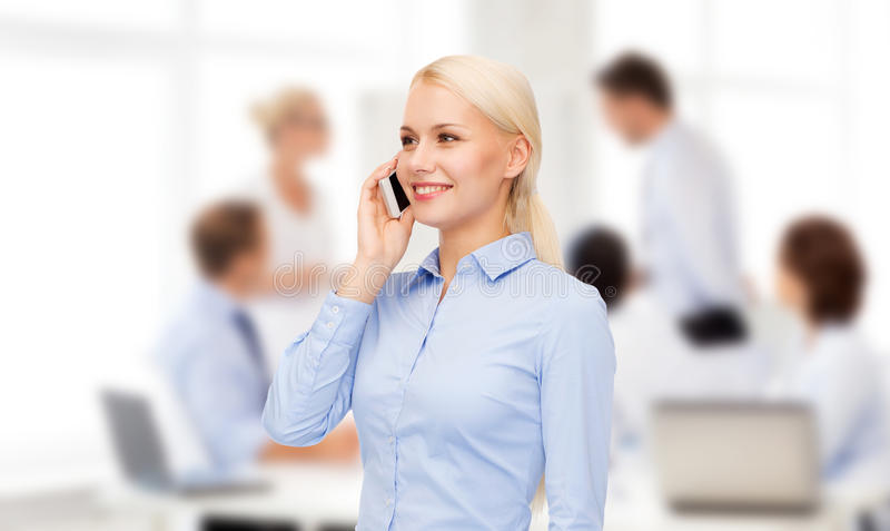 Young smiling businesswoman with smartphone. Business, technology and education concept - friendly young smiling businesswoman with smartphone royalty free stock photos