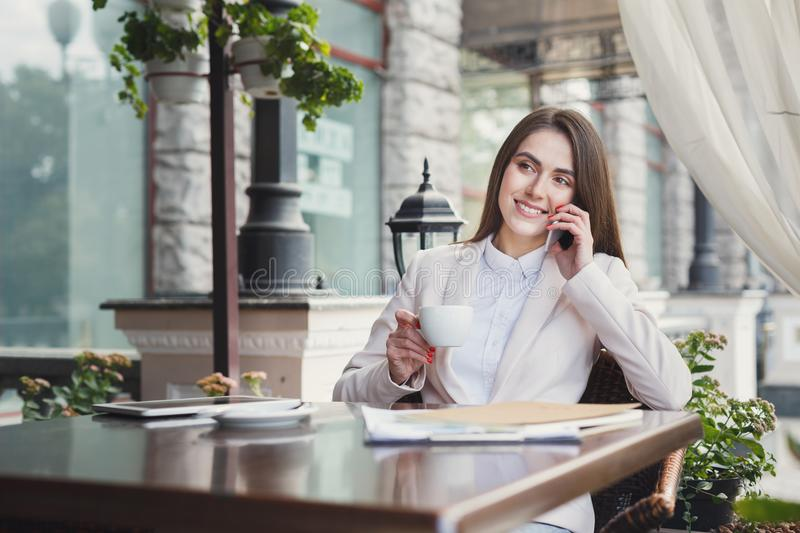 Young businesswoman talking on phone outdoors royalty free stock image