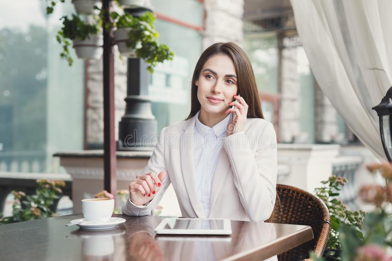 Young businesswoman talking on phone outdoors royalty free stock photography