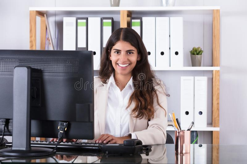 Smiling Businesswoman Typing On Keyboard royalty free stock photo