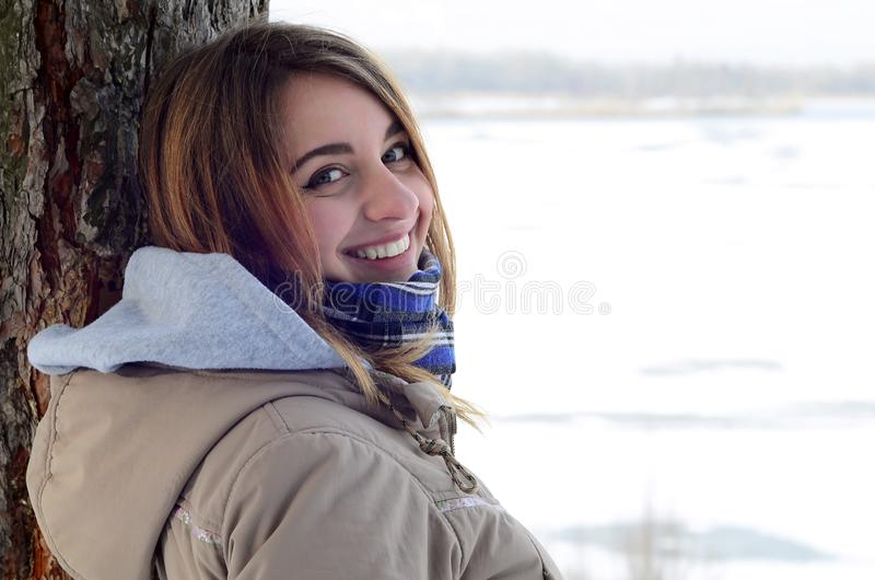 A young and smiling Caucasian girl looks around the horizon line stock image