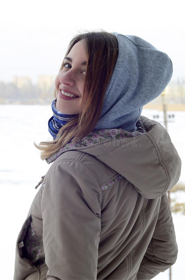 A young and smiling Caucasian girl looks around the horizon line between the sky and the frozen lake royalty free stock photo