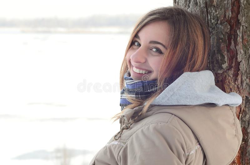 A young and smiling Caucasian girl looks around the horizon line between the sky and the frozen lake in winter time.  royalty free stock image