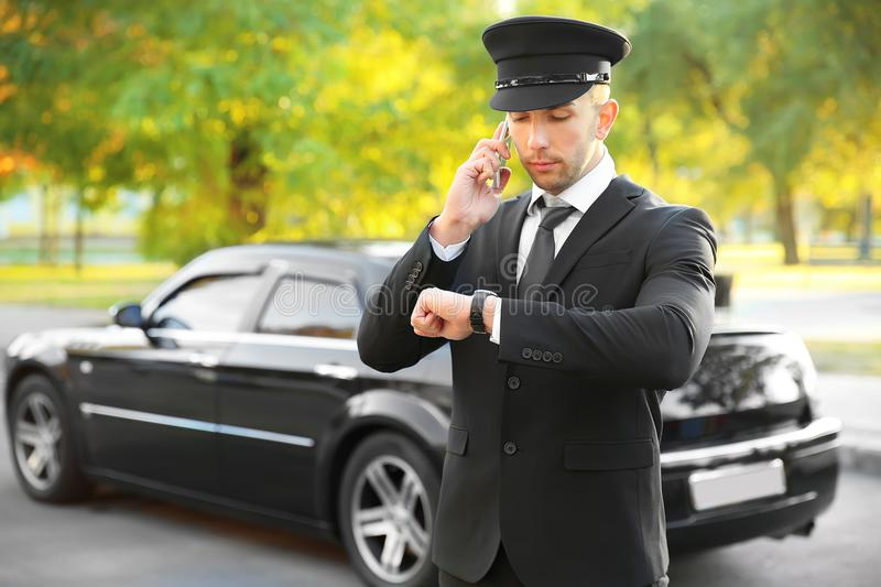 Young smiling chauffeur holding hat on background stock photos