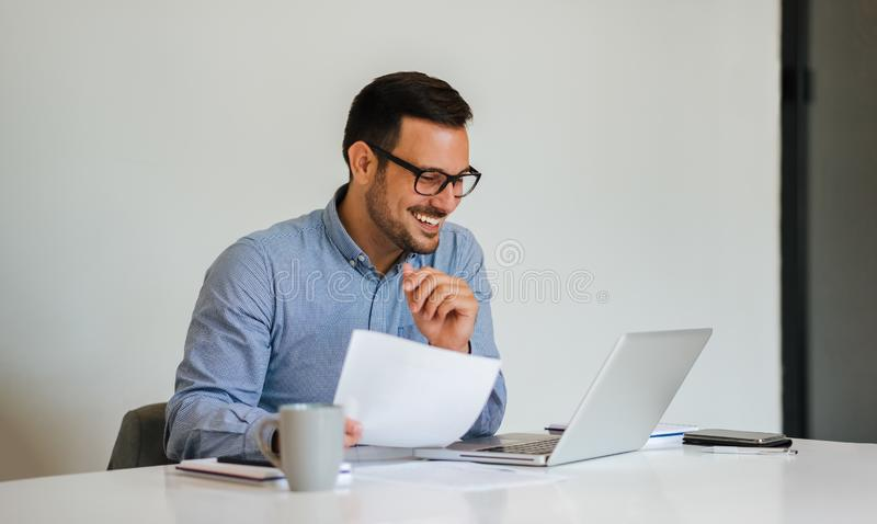 Young smiling cheerful businessman in office on video conference call.  stock image