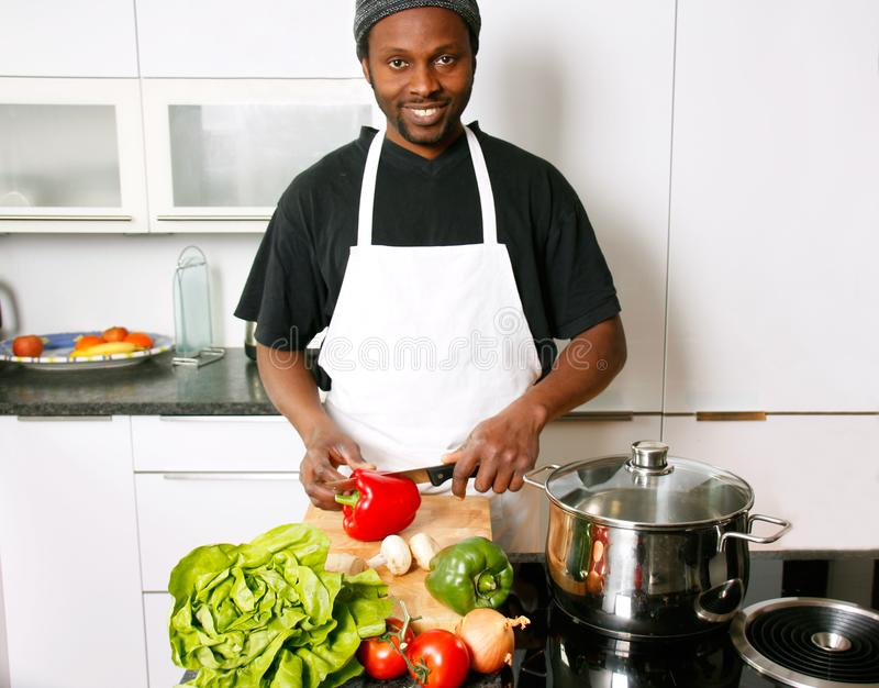 A young smiling chef cooking in the kitchen stock photo
