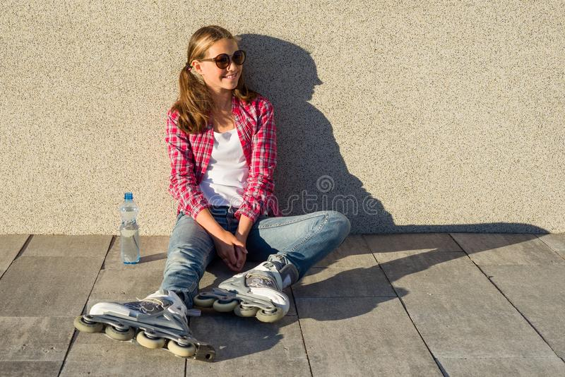 Young smiling cool girl shod in rollerblades, sits on the sidewalk and holding a water bottle. royalty free stock photography