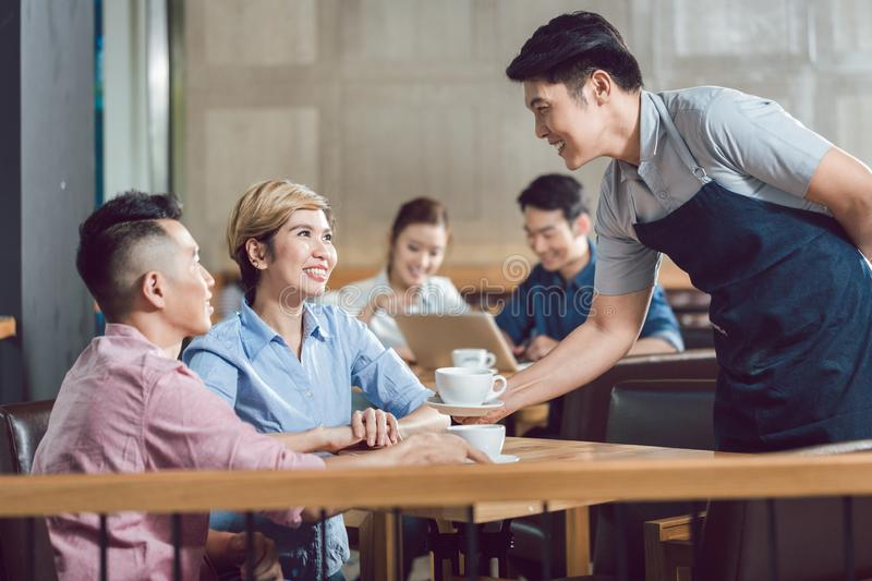 Couple being served with coffee in the cafe stock photos