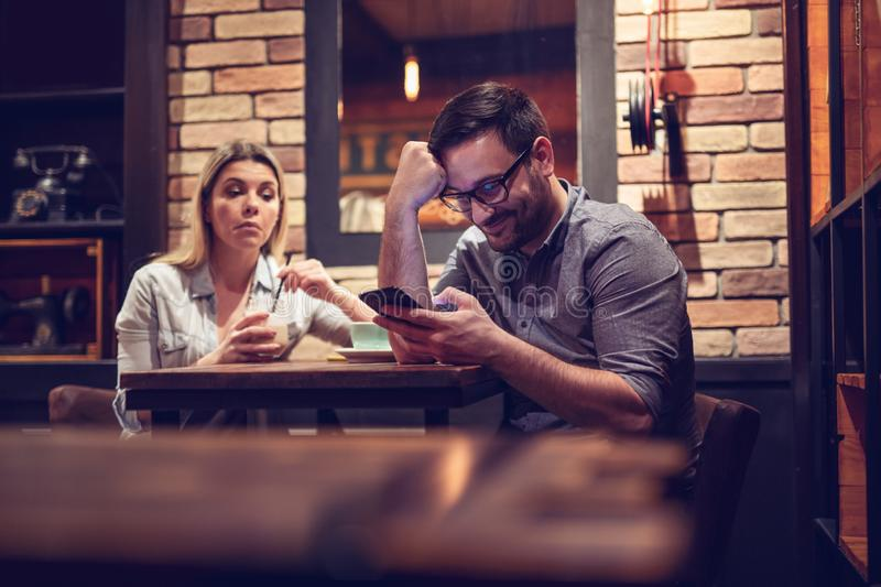 Young smiling couple in gorgeous restaurant. Man looking at phone. - Image stock photo