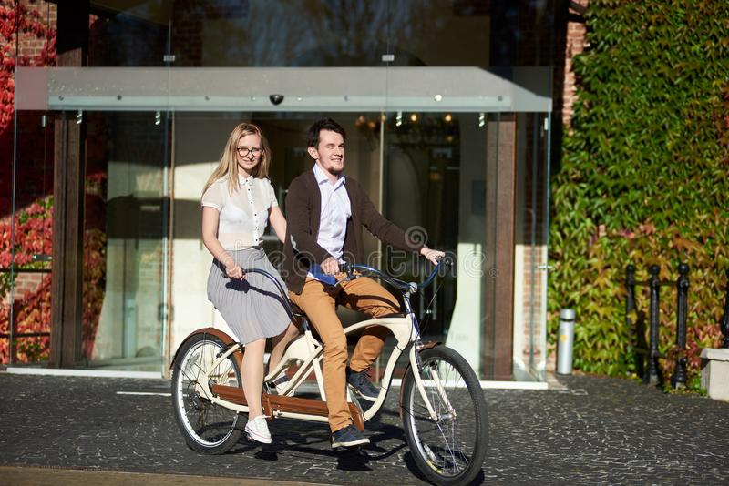 Young couple, handsome man and blond woman cycling tandem bike by building overgrown with red ivy. royalty free stock image