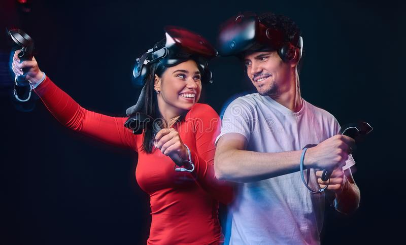 Young smiling couple having fun together, play with VR headsets and controllers. stock image