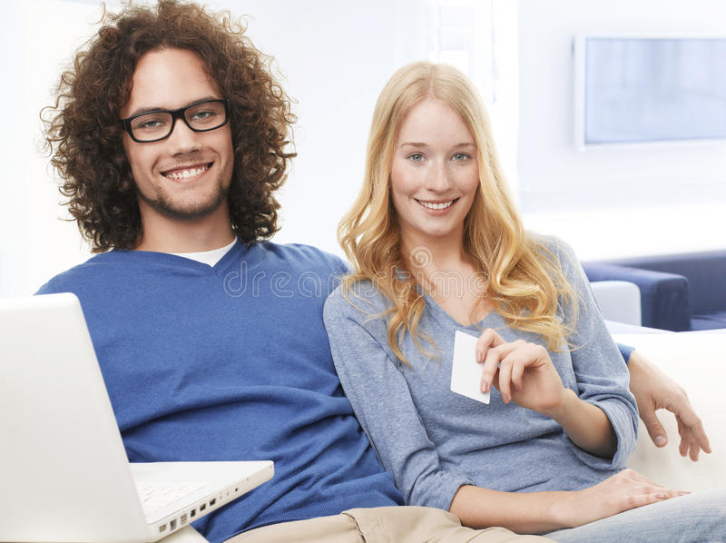 Young smiling couple using credit card and shopping on internet