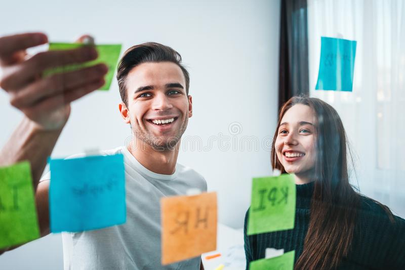 Young smiling coworking team post it notes sticky on glass wall while working and business meeting in office studio stock image