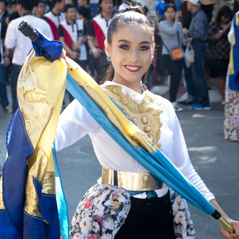 Young smiling dancing girl in traditional costume and a twirling flag. royalty free stock images