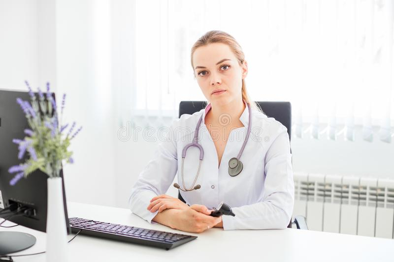 Young smiling doctor sitting at the desk on a black chair with her arms crossed stock photos