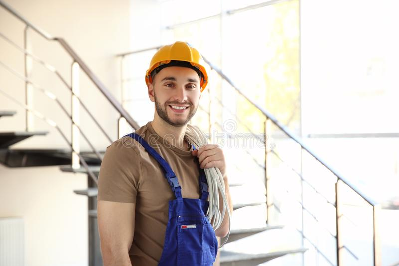 Young smiling electrician holding bunch of wires and standing royalty free stock photo