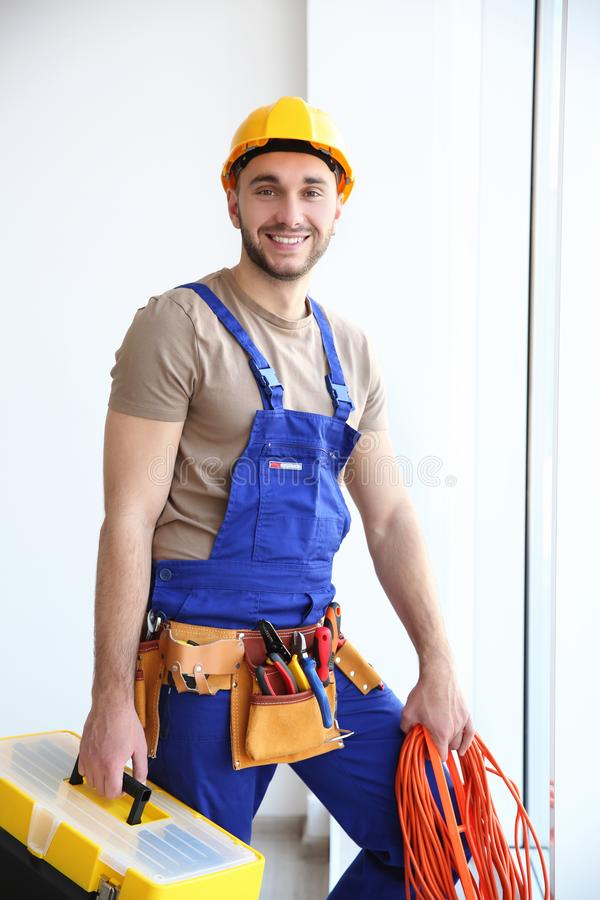 Young smiling electrician holding bunch of wires and tool box stock images