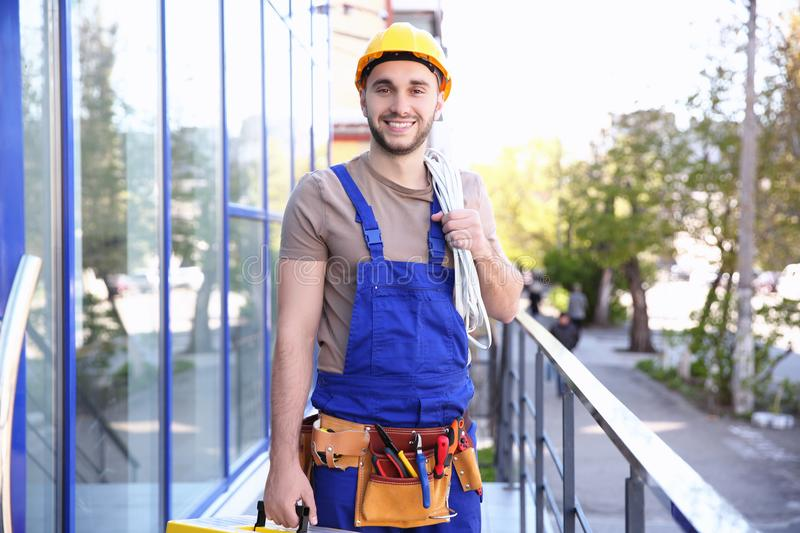 Young smiling electrician holding bunch royalty free stock photography