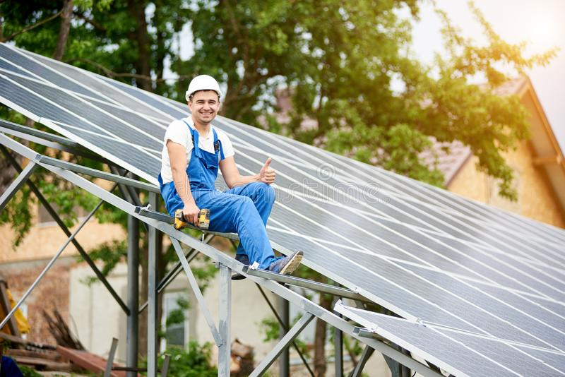 Installing of solar photo voltaic panel system. Young smiling electrician sitting on almost finished stand-alone solar photo voltaic panel system with stock photography