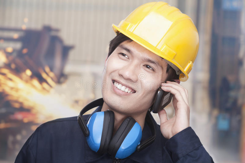 Young Smiling Engineer on the Phone wearing a Hardhat, On Site royalty free stock photo