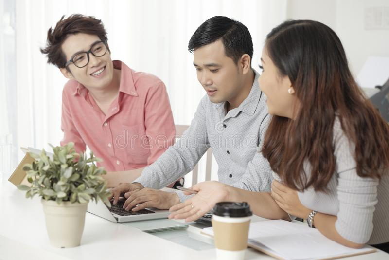 Contemporary Asian coworkers with laptop at desk stock images