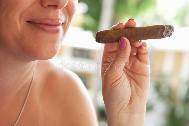 Young smiling European woman smokes cigar. Young smiling European woman smokes handmade cigar, closeup photo with selective focus. Dominican Republic stock images