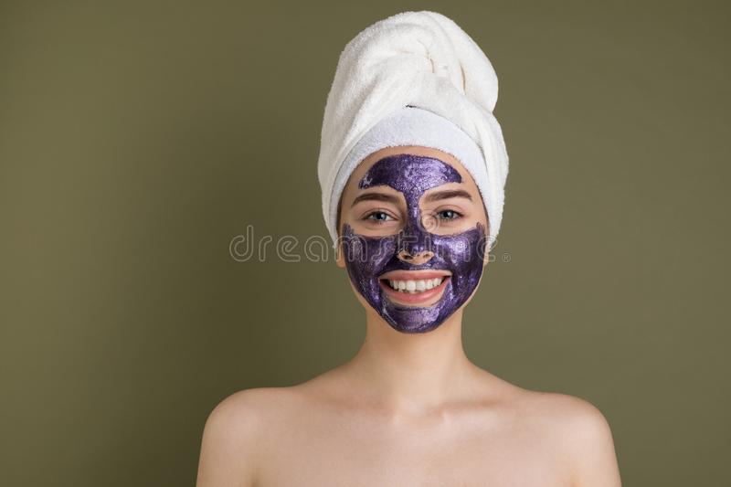 Young smiling european woman taking care of her face skin. Close up portrait of attractive girl with towel on her head and purple clay mask. Cosmetology stock image