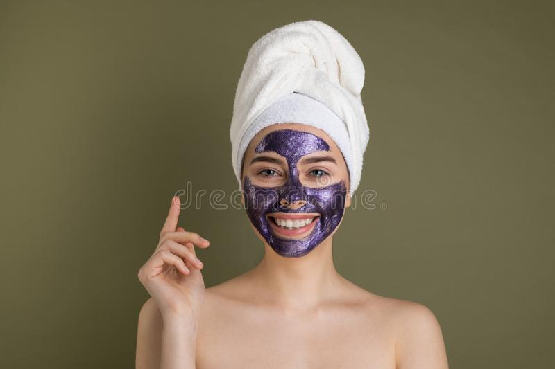 Young smiling european woman taking care of her face skin. Close up portrait of attractive girl with towel on her head and purple clay mask. Cosmetology stock photography