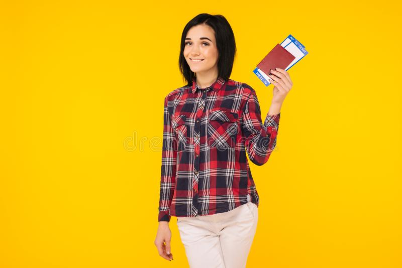 Young smiling excited woman student holding passport boarding pass ticket isolated on yellow background. stock photo